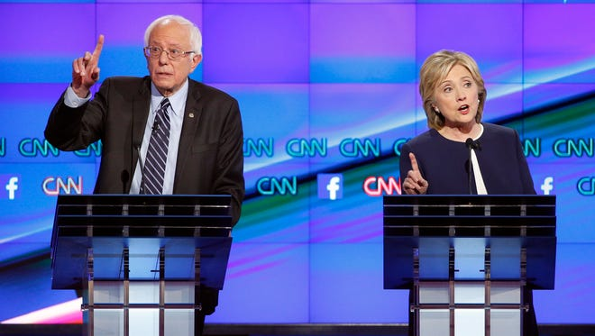 Democratic presidential candidates Hillary Clinton, right, and Sen. Bernie Sanders, I-Vt., speak during the Democratic presidential debate on Oct. 13 in Las Vegas.