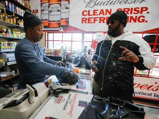 """Terrance """"Big T"""" Howard, 33, of Colerain Township, buys four oranges from the produce rack at Avondale Food Mart, Wednesday, March 8, 2017, in Cincinnati."""