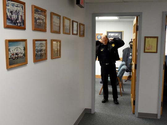 Chief Jim Williams of the Staunton Police Department slips into his coat as he prepares to leave his office on Thursday, Jan. 29, 2015.