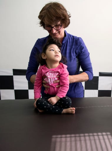(right) Claudia Funes watches her daughter Darah, 1, who was born with microcephaly after exposure to the Zika virus, during a session with physical therapist Ewa Lobos on Friday, March 16, 2018.
