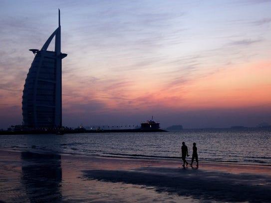 A couple strolls along Jumeirah beach near the Burj