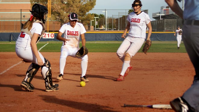 Glendale Ironwood catcher Macie Timmons, pitcher Hanna Gary and third basemen Maralee Whitey try to field a bunt in a game against Peoria Centennial.
