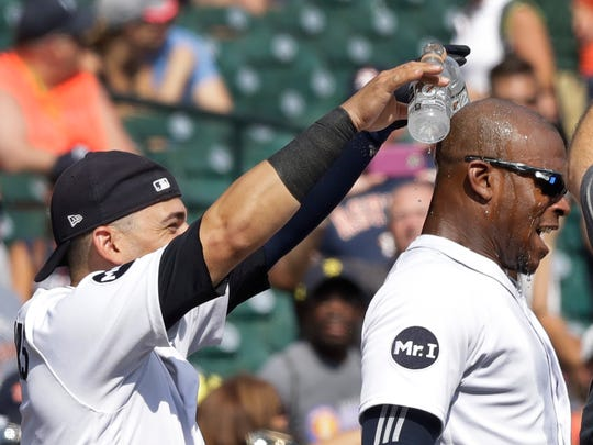 Tigers shortstop Jose Iglesias, left, pours a sports drink on leftfielder Justin Upton after the Tigers' 13-1 win over the Astros on Sunday, July 30, 2017, at Comerica Park.