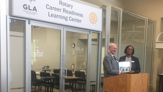 Rotarian George Fletcher presents Jocelyn Slaughter, executive director of Greenville Literacy Association, with a plaque on behalf of all of the club's centennial donors  in tribute to the centennial celebration.
