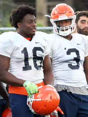 UTEP linebackers Alvin Jones, 16, and Dante Lovilotte, 3, rest on the sidelines during Tuesday's practice at Glory Field.