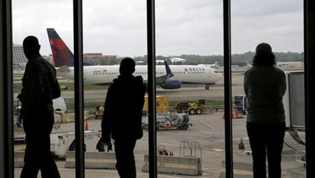 In this April 14, 2015, photo, Delta Air Lines passengers watch as a Delta plane taxis at Atlanta's Hartsfield International Airport in Atlanta. Delta Air Lines grounded flights scheduled to leave Monday, Aug. 8, 2016, after experiencing unspecified systems issues.