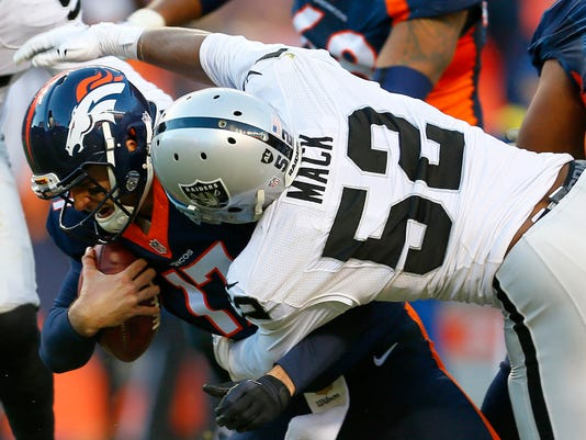 FILE - In this Dec. 13, 2015 file photo, Denver Broncos quarterback Brock Osweiler (17) is sacked by Oakland Raiders defensive end Khalil Mack (52) during the second half of an NFL football game in Denver. Oakland hasn't had a winning season since 2002, but the Raiders' roster is sprinkled with up-and-coming stars such as quarterback David Carr, receiver Amari Cooper and defensive lineman Khalil Mack.  (AP Photo/Joe Mahoney, File)