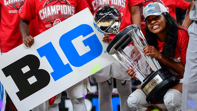 Ohio State Buckeyes forward Stephanie Mavunga (1) holds the trophy with her team as the background after winning the championship game during the Big Ten Conference Tournamentat Bankers Life Fieldhouse.