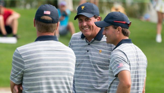 U.S. Team golfer Phil Mickelson smiles while talking to captain Steve Stricker and golfer Kevin Kisner.
