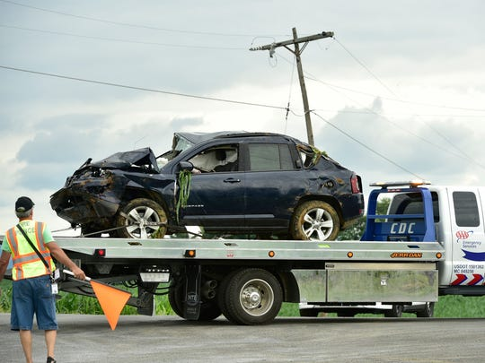 A late model Jeep Compass is hauled away after landing in a from a farmer's field Thursday, June 23, 2016 at Rice Road, Shippensburg. Two people were reportedly injured during the rollover crash.