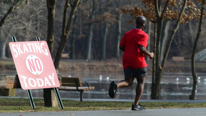 A man jogs around the pond, which is not iced over for skating. The unusual warm December weather brought people out to the Saddle River County Park in Glen Rock on December 27, 2016.  Tariq Zehawi/NorthJersey.com