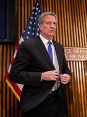 New York City Mayor Bill de Blasio exits a press conference in this October 25, 2018 file photo. De Blasio says he's turning the city into a model for how the nation can provide health care to all, including the poor, the uninsured and undocumented immigrants. But he may have promised more than he can deliver.