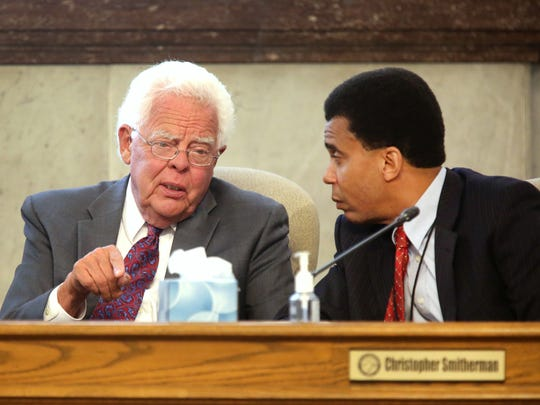 Cincinnati Councilmen David Mann, left, and Christopher Smithermen confer during council meeting where the Cincinnati Bell Connector was discussed and the need for additional streetcars this weekend.