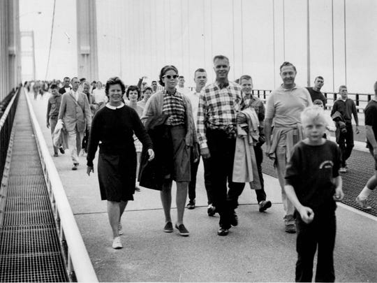 Governor G. Mennen (Soapy) Williams with wife Nancy walk in the first Mackinac bridge walk in late June 1958 during the Bridge's dedication ceremony.