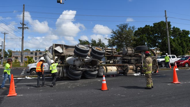Guam Police and Fire Department personnel block off northbound lanes on Marine Corps Drive in Dededo after a concrete mixer truck flipped.