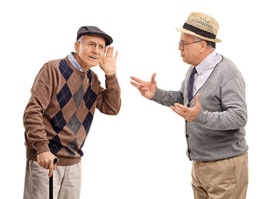 Senior man struggling to hear a friend in a discussion.