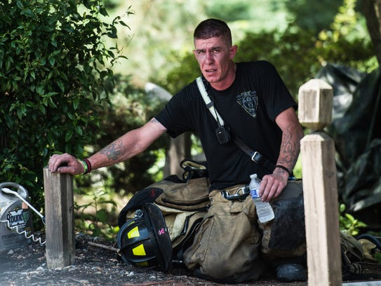 A firefighter takes a break in the shade as fire crews