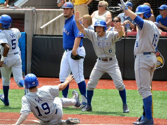 Kentucky's Matt Reida, center, celebrates as teammate Austin Cousino (19) slides in to score during the fourth inning of an NCAA college baseball regional tournament game in Louisville, Ky., Sunday, June 1, 2014. (AP Photo/Timothy D. Easley)