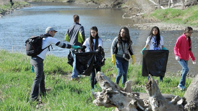 Volunteers clean up trash along the Hank Aaron State Trail and the Menomonee River as part of a past Work Play Earth Day event.