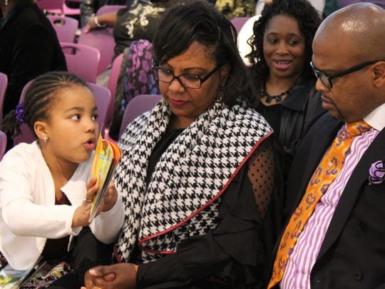 Iana NIckerson, 6, shows her parents, Sherita and Ian, a book she has read before Monday's event at the National Center for Chidlren's Illustrated Literature that honored the late Rev. Leo F. Scott. Rev. Nickerson later gave the benediction.