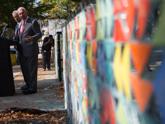 Wilmington Mayor Mike Purzycki looks back at a mosaic created by the Creative Vision Factory during a dedication for the piece Tuesday, Oct. 10, 2017 at Helen Chambers Park.