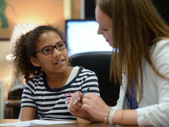 Megan Falish works with Alannah Sprewer as she crafts a thank you card at Tank Elementary School in Green Bay. Falish, who teaches second grade, is finishing up her first school year in the profession.