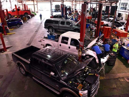 Technicians work on vehicles in the Arrow Ford service bay Jan. 9. The Abilene dealership was awarded Small Employer of the Year for 2017.