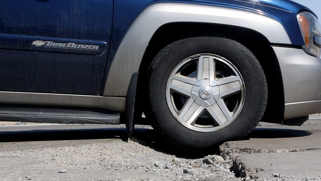 A Chevy TrailBlazer SUV slowly creeps through a pothole while driving down Northwestern Highway near 8 Mile Road in Southfield on Wednesday, March 26, 2014.