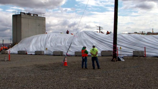 Hanford workers install a cover over Tunnel 1 at the PUREX facility.