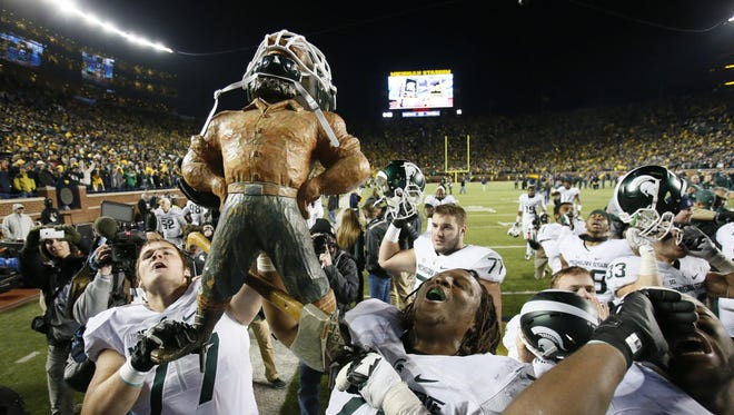 Michigan State offensive linemen Nick Padla, left, and Donavon Clark parade around the Paul Bunyan Trophy as they sing the fight song after a shocking 27-23 victory over Michigan in the Big House in 2015.