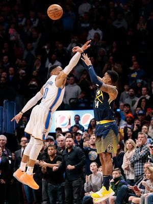 Denver Nuggets guard Gary Harris (14) scores the game winning basket as Oklahoma City Thunder guard Russell Westbrook (0) defends in the final seconds of the fourth quarter at the Pepsi Center.
