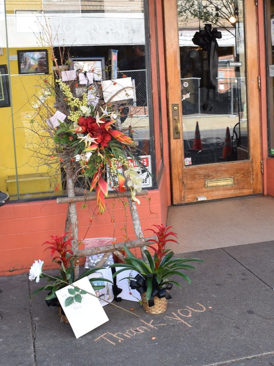 Black ribbons are hung at Tamp & Grind Coffee House in downtown Alexandria and a makeshift memorial outside the shop honoring the owner, the late Jeff Phillips, is growing.