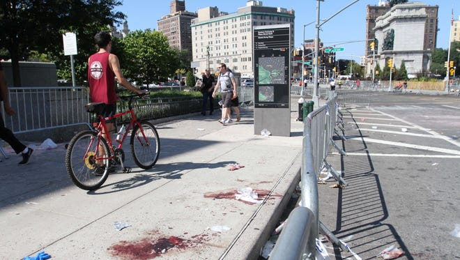 Blood stains remain on a sidewalk, Monday, Sept. 7, 2015, where earlier a 24-year-old man was stabbed to death at Grand Army Plaza in the Brooklyn borough of New York, before the start of the West Indian Day Parade. (AP Photo/Tina Fineberg)