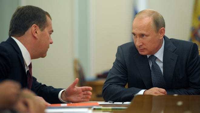 Russian President Vladimir Putin listens to Russian Prime Minister Dmitry Medvedev, left, during the Security Council meeting in the Novo-Ogaryovo residence, outside Moscow, Russia, Monday.