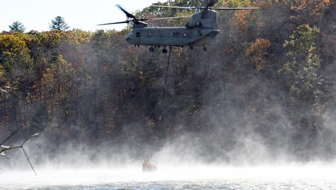 A helicopter tries to get water Saturday in an effort to contain the fire at Pinnacle Mountain