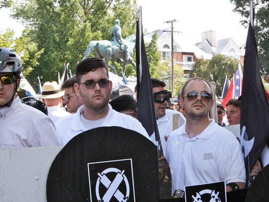 James Alex Fields Jr., second from left, holds a black shield in Charlottesville, Va., where a white supremacist rally took place. Fields was later charged with second-degree murder, three counts of malicious wounding and one count of hit and run after authorities say he plowed a car into a crowd of people protesting the white nationalist rally.