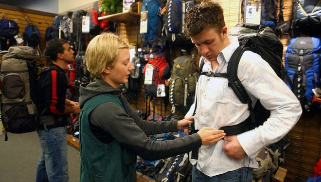 REI worker Elizabeth Kautzman, middle, helps Zach Ogle try out a backpack at the Fort Collins store in this file photo. REI plans to expand its College Avenue store into an adjacent space.