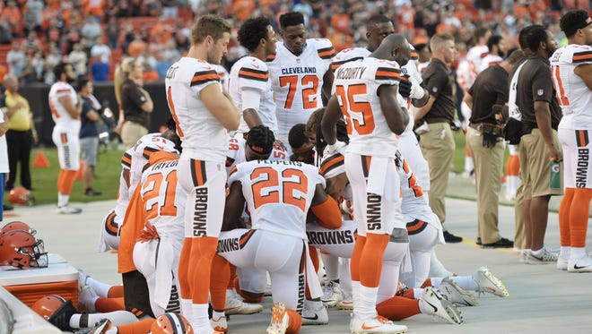Members of the Cleveland Browns kneel during the national anthem before a preseason game against the New York Giants at FirstEnergy Stadium.