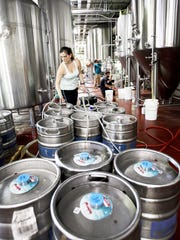 Sarah Gulotta fills kegs at Hi-Wire Brewing June 23.