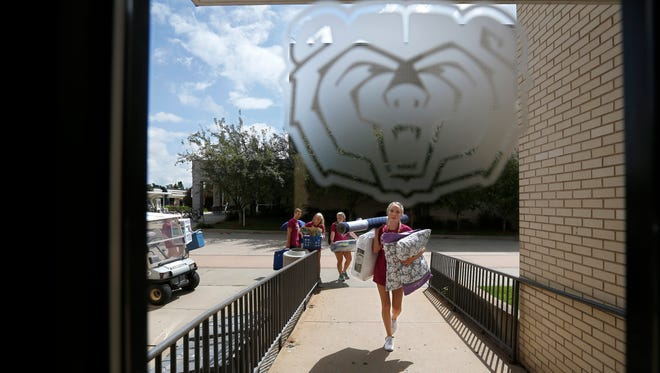 Morgan Bigge, of Sigma Kappa, front, helps a new student carry their belongings into the dorms during move-in-day on the MSU campus on Friday, August 19, 2016.