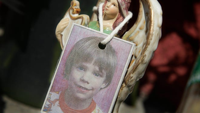 A photograph of Etan Patz hangs on an angel figurine, part of a makeshift memorial in the SoHo neighborhood of New York, on May 28, 2012.