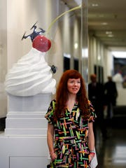 Artist Heather Phillipson poses for the media at the National Gallery in London, Tuesday, March 21, 2017, next to her winning design entitled 'The End' for one of the next two Fourth Plinth sculptures in Trafalgar Square, which will be unveiled on the plinth in 2018 and 2020.