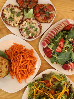 A sampling of nutritionally balanced meals at BFF Café (clockwise from top): cauliflower bread pizzas, ahi salad, a vegetable zoodle (noodle) salad, and a cauliflower bread bison burger with sweet potato fries.