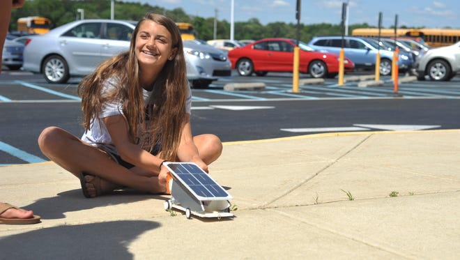 Alia Marshall shows off the model solar-powered vehicle she helped design, which won 5th place at the 20th Annual Junior Solar Sprint May 13.