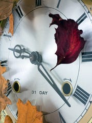 Close-up of antique clock surrounded with fall leaves.