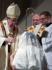 Archbishop of Detroit Allen H. Vigneron places a veil