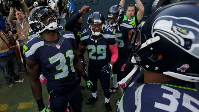 "Seattle Seahawks ""Legion of Boom"" defensive players including Kam Chancellor (31) and Earl Thomas (29) huddle before taking the field before an NFL football game against the Detroit Lions, Monday, Oct. 5, 2015, in Seattle. Both teams are wearing pink items for breast cancer awareness during the game."
