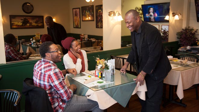 Patrick Howell, owner of Little Negril Jamaican Restaurant, talks with customers Tivern and Lezley Turnbull. For Storefront. Tuesday, December 23, 2014.