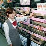 In this Oct. 31, 1998 photo, a salesclerk shows high quality VHS video casette recorders at a home and electrical appliance store in Osaka. Japanese electronics maker Funai Electric Co. says it's yanking the plug on the world's last video cassette recorder.