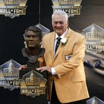 Former NFL player Mick Tingelhoff poses with his bust during an induction ceremony Saturday at the Pro Football Hall in Canton, Ohio.
